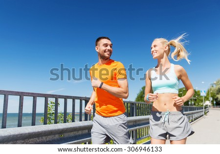 fitness, sport, friendship and healthy lifestyle concept - smiling couple with heart-rate watch running at summer seaside - stock photo