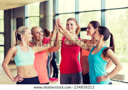 fitness, sport, friendship and lifestyle concept - group of women making high five gesture in gym - stock photo
