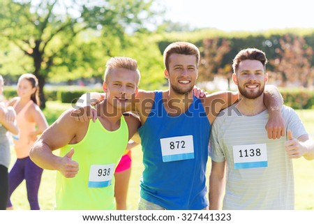 fitness, sport, friendship, gesture and healthy lifestyle concept - group of happy teenage friends or sportsmen with racing badge numbers showing thumbs up at marathon outdoors - stock photo