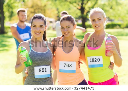 fitness, sport, friendship, marathon and healthy lifestyle concept - happy young sporty women with racing badge numbers and water bottles outdoors - stock photo