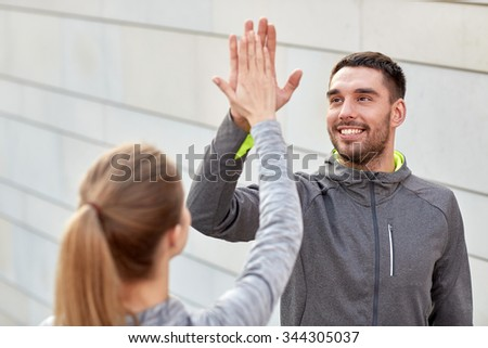 fitness, sport, gesture, people and success concept - happy couple giving high five outdoors - stock photo
