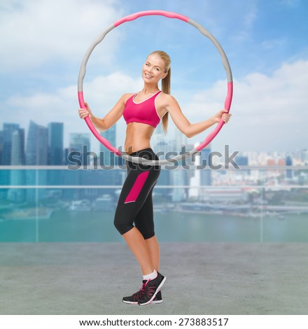 fitness, sport, people and healthcare concept - young sporty woman exercising with hula hoop over city waterside background - stock photo