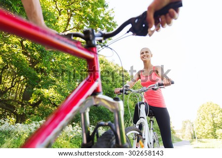 fitness, sport, people and healthy lifestyle concept - close up of happy couple riding bicycle outdoors at summer - stock photo