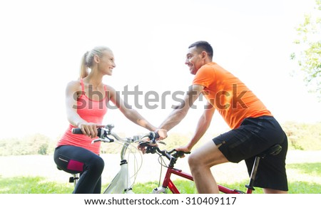 fitness, sport, people and healthy lifestyle concept - happy couple riding bicycle outdoors at summer - stock photo