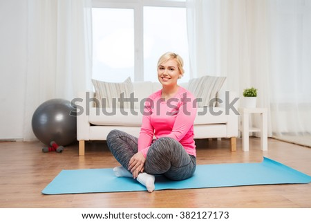 fitness, sport, people and healthy lifestyle concept - happy plus size woman sitting on mat at home - stock photo