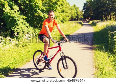 fitness, sport, people and healthy lifestyle concept - happy young man riding bicycle outdoors - stock photo