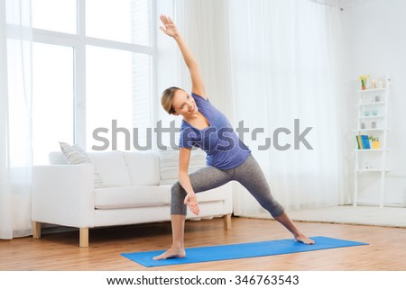 fitness, sport, people and healthy lifestyle concept - woman making yoga bikram triangle pose on mat - stock photo