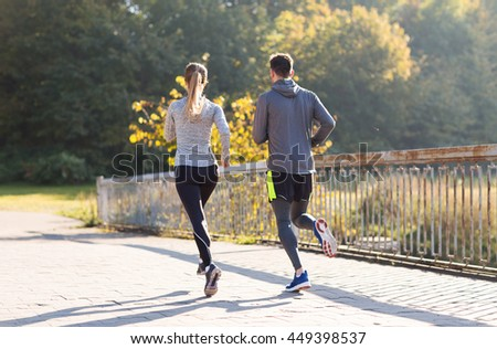 fitness, sport, people and jogging concept - couple running or jogging outdoors - stock photo
