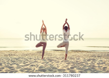 fitness, sport, people and lifestyle concept - couple making yoga exercises on sand outdoors from back - stock photo