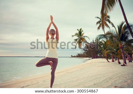 fitness, sport, people and lifestyle concept - young woman making yoga exercises on beach from back - stock photo