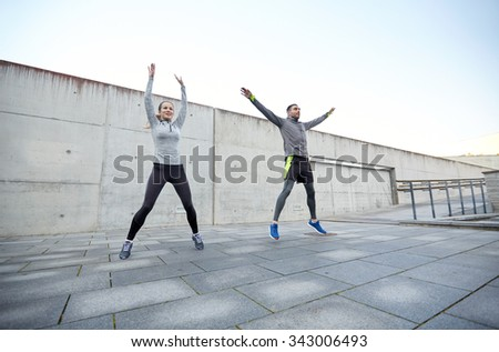 fitness, sport, people, exercising and lifestyle concept - happy man and woman jumping outdoors - stock photo