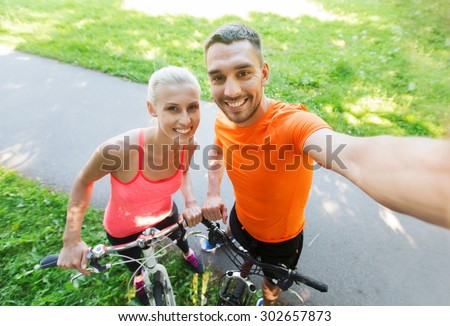 fitness, sport, people, technology and healthy lifestyle concept - happy couple with bicycle taking selfie outdoors - stock photo