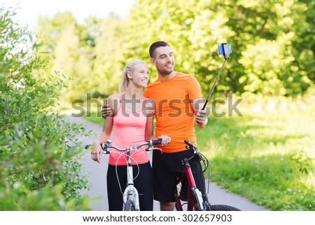 fitness, sport, people, technology and healthy lifestyle concept - happy couple with bicycle taking picture by smartphone on selfie stick outdoors - stock photo