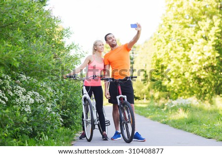 fitness, sport, people, technology and healthy lifestyle concept - happy couple with bicycle taking selfie by smartphone outdoors - stock photo