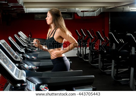fitness, sport, power-lifting and people concept - a nice girl running on a treadmill at the gym - stock photo