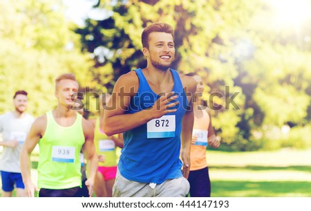 fitness, sport, race and healthy lifestyle concept - group of happy teenage friends or sportsmen running marathon with badge numbers outdoors - stock photo
