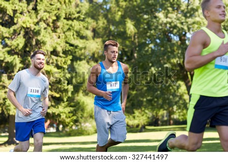 fitness, sport, race and healthy lifestyle concept - group of happy teenage sportsmen running marathon with badge numbers outdoors - stock photo