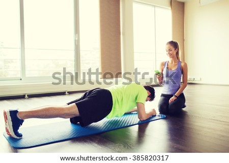 fitness, sport, technology and people concept - man and woman with smartphone doing plank exercise on mat in gym - stock photo