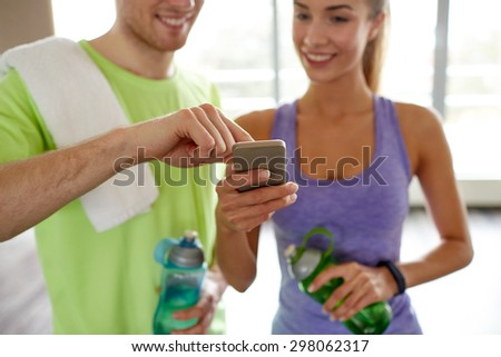 fitness, sport, technology and slimming concept - close up of smiling young woman and personal trainer with smartphone and water bottles in gym - stock photo