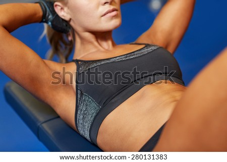 fitness, sport, training and lifestyle concept - close up of woman flexing abdominal muscles on bench in gym - stock photo