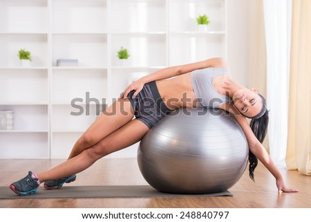 Fitness, sport, training and lifestyle concept. Pretty woman with exercise ball at home. - stock photo