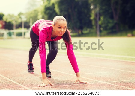 fitness, sport, training and lifestyle concept - smiling african american woman running on track outdoors - stock photo