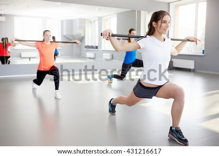 fitness, sport, training and lifestyle concept. Sporty young women exercising at fitness studio. pilates, bar - stock photo