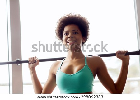 fitness, sport, training and people concept - happy smiling african american woman holding bar in gym - stock photo