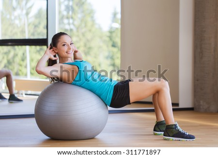 fitness, sport, training and people concept - smiling woman flexing abdominal muscles with exercise ball in gym - stock photo