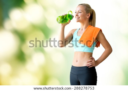 fitness, sport, training, drink and lifestyle concept - woman with bottle of water and towel over green natural background - stock photo