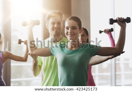 fitness, sport, training, gym and lifestyle concept - group of happy women and trainer with dumbbells flexing muscles in gym - stock photo