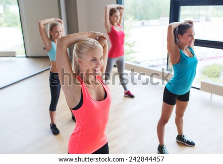 fitness, sport, training, gym and lifestyle concept - group of happy women working out and stretching shoulder in gym - stock photo