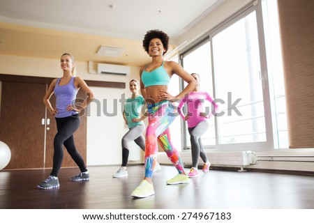 fitness, sport, training, gym and lifestyle concept - group of happy women working out and stretching leg in gym - stock photo