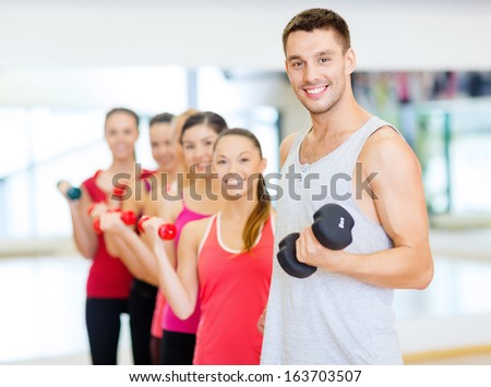 fitness, sport, training, gym and lifestyle concept - group of smiling people lifting dumbbells in the gym - stock photo