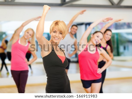 fitness, sport, training, gym and lifestyle concept - group of smiling people with trainer exercising in the gym - stock photo