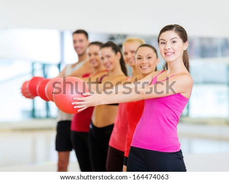 fitness, sport, training, gym and lifestyle concept - group of smiling people working out with stability balls in the gym - stock photo
