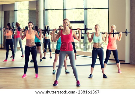 fitness, sport, training, gym and lifestyle concept - group of women with barbells in gym - stock photo