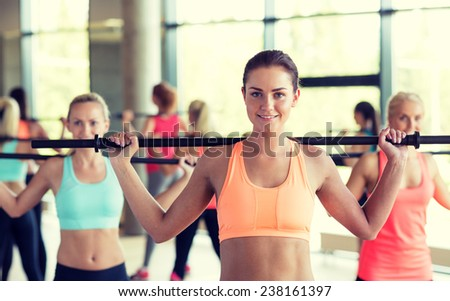 fitness, sport, training, gym and lifestyle concept - group of women with bars in gym - stock photo