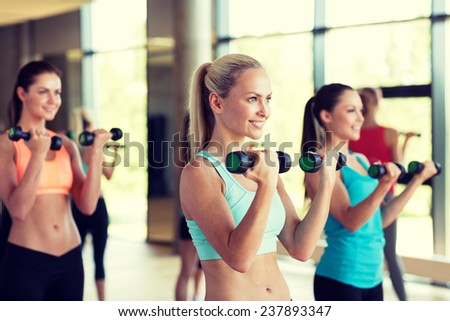 fitness, sport, training, gym and lifestyle concept - group of women with dumbbells in gym - stock photo
