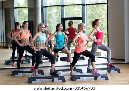 fitness, sport, training, gym and lifestyle concept - group of women working out with steppers in gym - stock photo