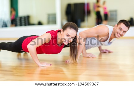 fitness, sport, training, gym and lifestyle concept - smiling couple doing push-ups in the gym - stock photo