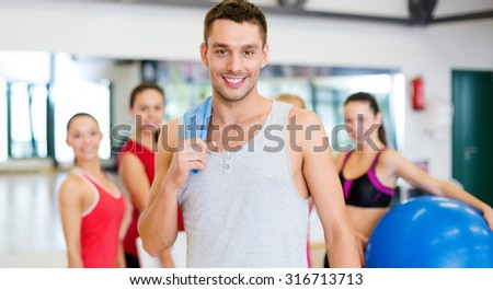 fitness, sport, training, gym and lifestyle concept - smiling man standing in front of the group of people in gym - stock photo