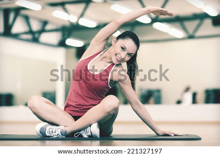 fitness, sport, training, gym and lifestyle concept - smiling woman stretching on mat in the gym - stock photo
