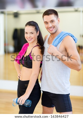 fitness, sport, training, gym and lifestyle concept - two smiling people in the gym - stock photo