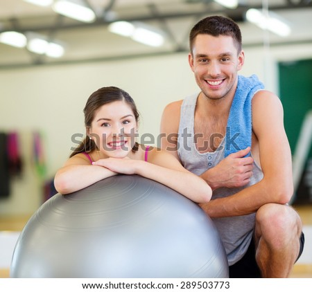 fitness, sport, training, gym and lifestyle concept - two smiling people with fitness ball in the gym - stock photo
