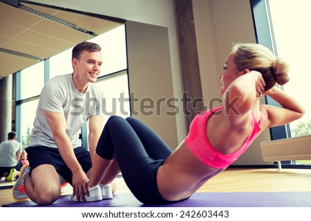 fitness, sport, training, gym and lifestyle concept - woman with personal trainer doing sit ups in gym - stock photo