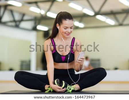 fitness, sport, training, gym, technology and lifestyle concept - smiling woman with smartphone - stock photo
