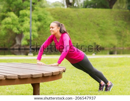 fitness, sport, training, park and lifestyle concept - smiling african american woman doing push-ups on bench outdoors - stock photo