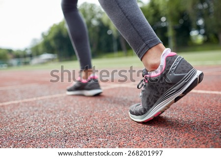fitness, sport, training, people and lifestyle concept - close up of woman feet running on track from back - stock photo