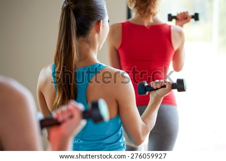 fitness, sport, training, people and lifestyle concept - close up of women working out with dumbbells and flexing muscles in gym - stock photo
